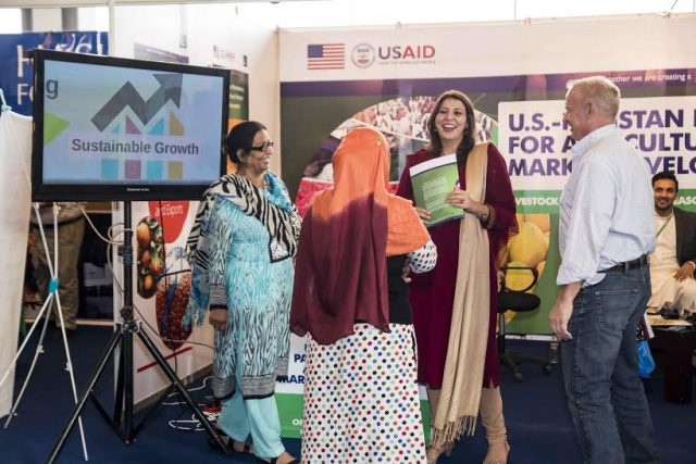 Mubarika (center) and CNFA Cheif of Party, Peter Dickrell, speak with women entrepreneurs and exporters at the WEXNET expo in Lahore, Pakistan.