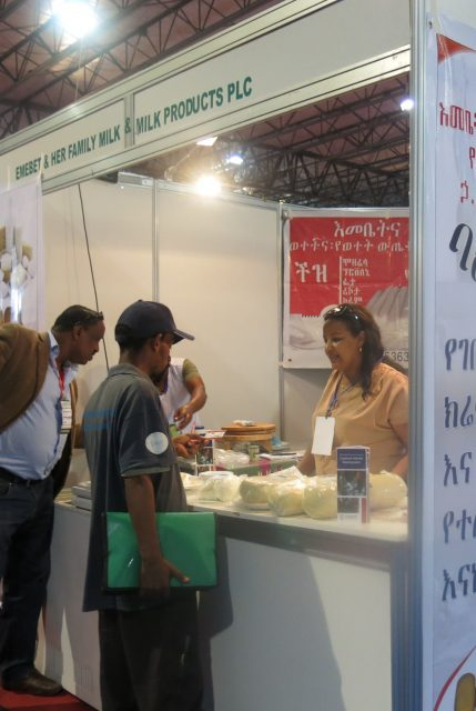 Emebet addressing clients at a trade show