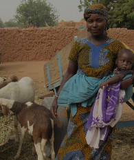 Woman holding child next to goat